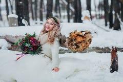 斯拉夫的出现的逗人喜爱的新娘与花圈的拿着花束,在注册旁边坐多雪的森林婚礼 免版税库存照片