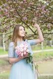 斯拉夫的女孩在春天在公园 佐仓开花背景 免版税库存照片