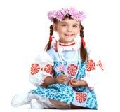 斯拉夫的服装和花圈的愉快的小女孩 免版税库存照片