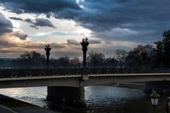 斯科普里、马其顿- 2017年12月9日-市中心和一座桥梁在河瓦尔达尔河日落的 免版税库存图片