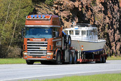斯科讷144拖拉沿高速公路的一条消遣小船 免版税图库摄影