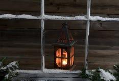 斯诺伊与发光的灯笼的窗口和冷杉分支 免版税库存照片