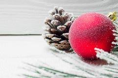 斯诺伊分支圣诞树和锥体和红色球在白色木葡萄酒背景 免版税图库摄影