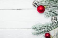 斯诺伊分支圣诞树和锥体和红色球在白色木葡萄酒背景 图库摄影