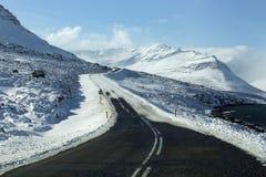 斯诺伊和冰冷的路有火山的山的冬天 免版税库存照片