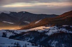 斯诺伊在日出的山小山 库存图片