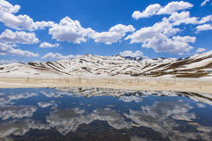 斯诺伊山和反射在水中 免版税库存照片