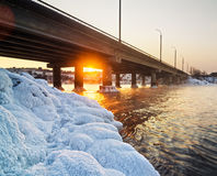 斯诺伊桥梁和美好的冷淡的日落在河在冬天 免版税库存图片