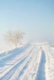 斯诺伊空的被铲起的乡下路在日出的一个有雾的冬天早晨 免版税图库摄影