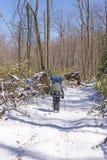 斯诺伊足迹的背包徒步旅行者在春天雪以后 免版税库存照片