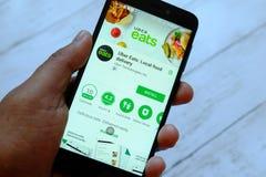 斯里巴加湾市,文莱- 2018年7月25日, :拿着有Uber的一只男性手智能手机吃在机器人谷歌戏剧商店的app 免版税图库摄影