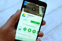 斯里巴加湾市,文莱- 2018年7月25日, :拿着有谷歌驱动的app的一只男性手智能手机在机器人谷歌戏剧商店 免版税库存图片
