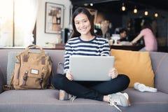 新一代使用膝上型计算机的亚洲人妇女在咖啡店,亚洲wo 免版税库存图片