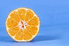 新一半切了在蓝色木桌上的桔子 免版税库存照片