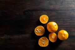 新一半切了在黑暗的木桌上的桔子 免版税库存图片