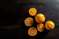 新一半切了在黑暗的木桌上的桔子 免版税库存照片