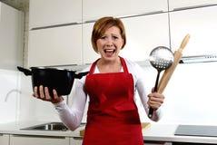 新人家厨师妇女在举行烹调的红色围裙在家厨房里平底锅和滚针尖叫绝望在重音 免版税库存图片