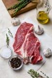新伐牛肉用在轻的米黄背景的草本 免版税库存图片