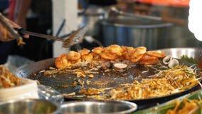 新作鲜美垫泰国特写镜头,慢动作 厨师从铁锅,炸虾取消完成的食物是 股票录像