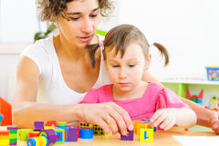 新使用与玩具块的母亲和小女儿 免版税库存图片
