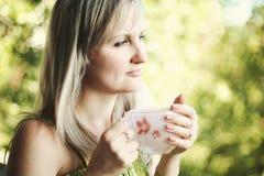 新俏丽的妇女饮用的咖啡 免版税库存图片