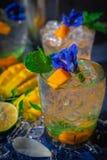 新冰芒果苏打饮料由蓝色蝴蝶豌豆花装饰,并且在那里木桌上的薄菏是芒果切片,冰,柠檬, 库存照片