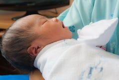 新出生亚裔睡着的表面秋天的女性 免版税库存照片