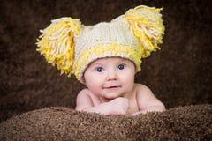 新出生在米黄背景的被编织的冬天帽子 免版税库存照片