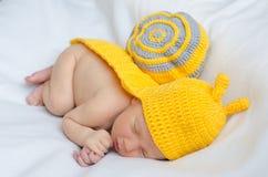 新出生在蜗牛衣服 免版税库存照片