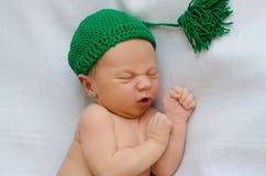 新出生在绿色被编织的帽子 图库摄影