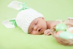 新出生婴孩兔宝宝盖帽穿戴的复活节彩蛋 免版税库存图片