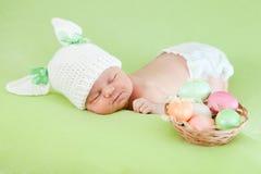 新出生婴孩兔宝宝盖帽穿戴的复活节彩蛋 库存照片