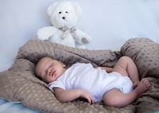 新出生婴孩睡觉全长与白色玩具熊在背景中 免版税图库摄影