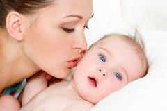 新出生婴孩逗人喜爱的愉快的母亲 免版税库存照片
