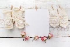 新出生或洗礼贺卡 与女婴鞋子和手套的空白在白色木背景 免版税库存照片