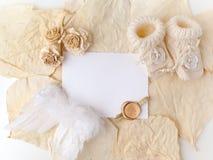 新出生或洗礼贺卡 与女婴鞋子的白纸在biege背景 平的位置 顶视图 免版税库存照片