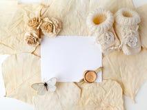 新出生或洗礼贺卡 与女婴鞋子的白纸在biege背景 平的位置 顶视图 库存图片