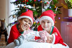 新出生的女婴和两个更老的兄弟在圣诞树附近哄骗圣诞老人帽子的男孩 库存图片