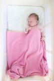 新出生的女孩在旅行小儿床睡觉 免版税图库摄影