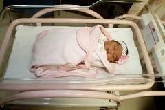新出生的女孩在医院病床上 免版税库存照片