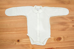 新出生的女孩的衣裳木背景的 图库摄影