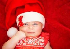 新出生的女孩穿戴圣诞老人帽子 图库摄影