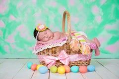 新出生的女婴有在柳条筐的美梦 背景美丽的复活节彩蛋节假日污点 免版税图库摄影