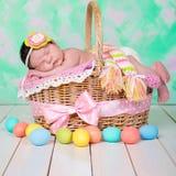 新出生的女婴有在柳条筐的美梦 背景美丽的复活节彩蛋节假日污点 库存照片