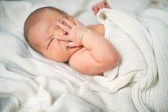 新出生的婴孩用在她的说谎在床上的面孔的一只手,盖由一条白色毯子 免版税库存照片