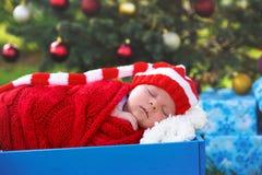 新出生的婴孩画象圣诞老人的给说谎穿衣在圣诞节下 库存照片