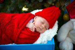 新出生的婴孩画象圣诞老人的给说谎穿衣在圣诞节下 免版税库存图片
