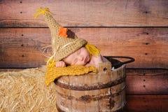 新出生的男婴佩带的稻草人服装 库存图片