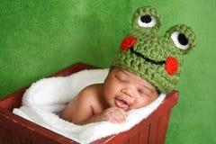 新出生的男婴佩带的青蛙帽子 库存图片