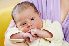 新出生的婴孩半眯着的眼睛  免版税图库摄影